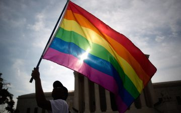 Carlos McKnight, from Washington, D.C., waves a rainbow colored flag outside the U.S. Supreme Court in Washington, D.C., U.S., on Friday, June 26, 2015. The high court will decide by the end of the month whether the Constitution gives gays the right to marry. The court's actions until now have suggested that a majority of the nine justices will vote to legalize same-sex weddings nationwide. Photographer: Andrew Harrer/Bloomberg *** Local Caption *** Carlos McKnight